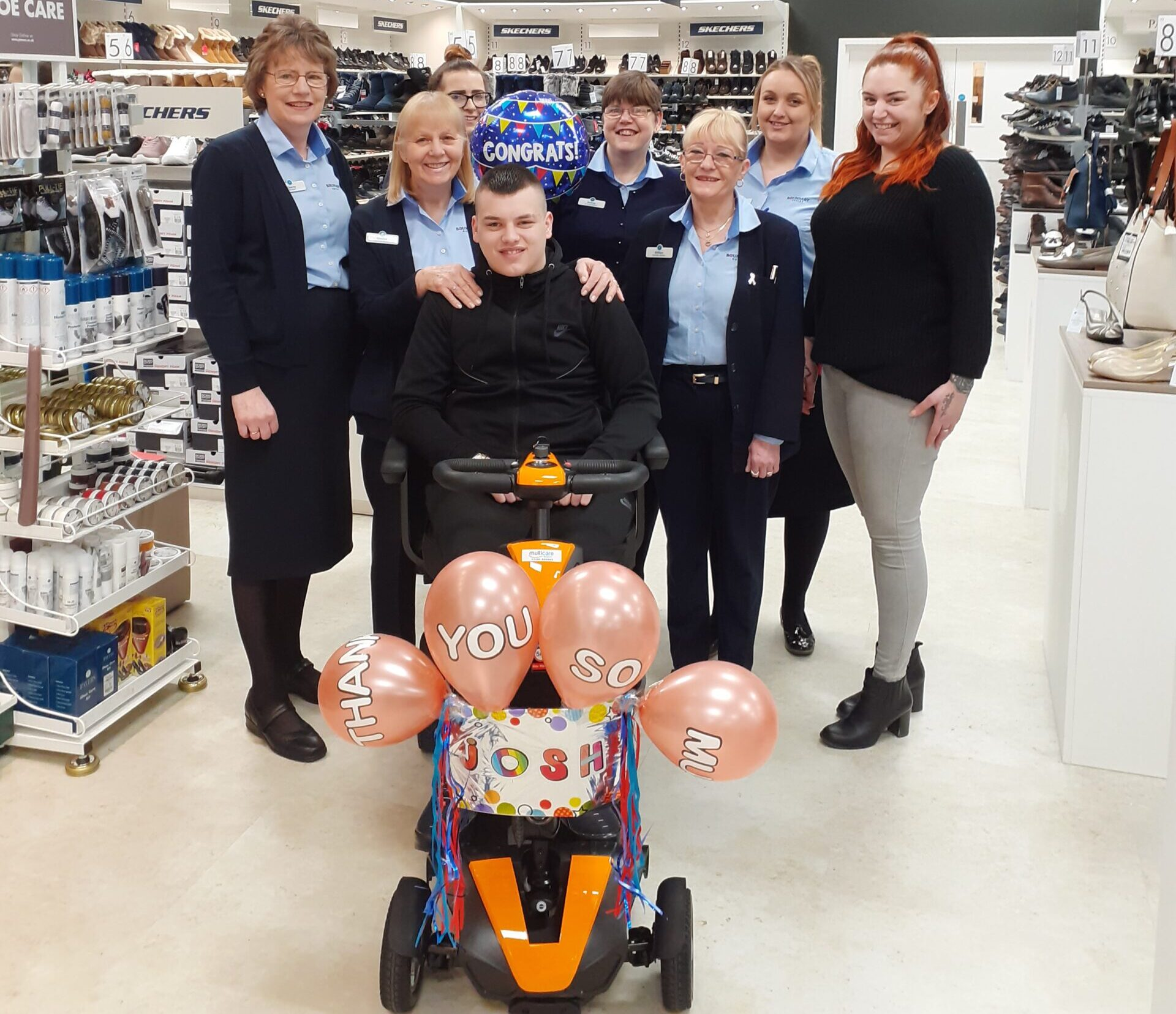 Joshua on his new mobility scooter with the team at Pavers in Colne