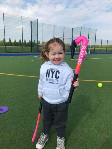 A young female member of the club holding two hockey sticks with a smile on her face.