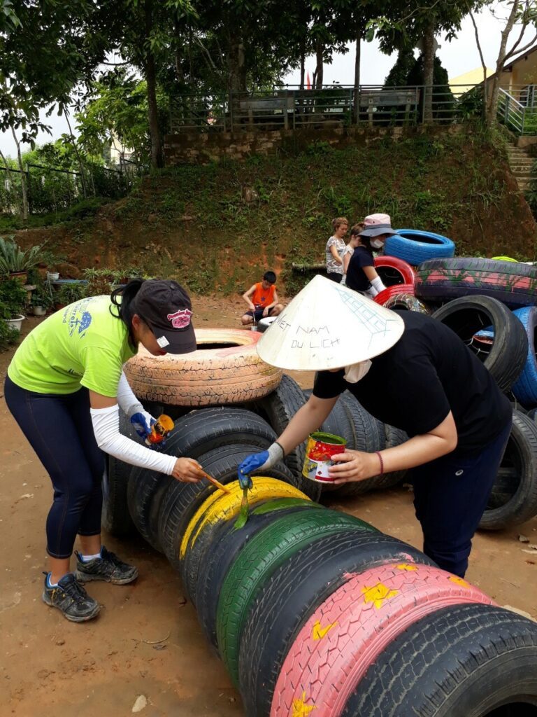 Volunteers painting tyres bright colours